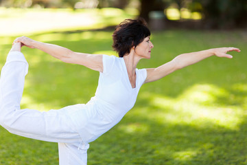 mid aged woman doing yoga pose outdoors