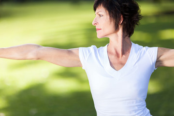 middle aged woman doing exercise outdoors