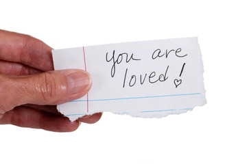 Hand holding note that reads 'You Are Loved'