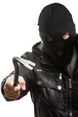 Criminal thief or burglar man in balaclava or mask holding crowb