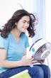 Beautiful young woman or teen enjoying cool fan breeze