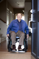 Elderly man in wheelchair at his front door