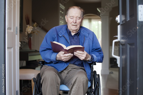 Elderly man in wheelchair at his front door reading the Bible