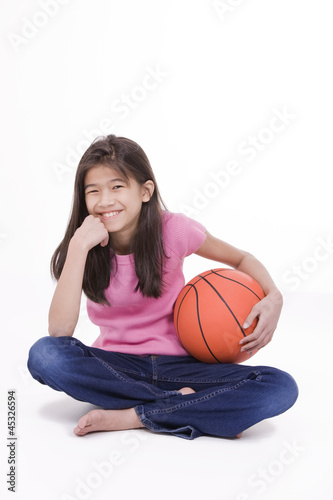 Ten year old Asian girl holding basketball, isolated on white