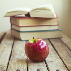 Fresh apple on wooden table with old books