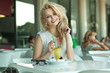 Young cheerful blonde in a drink bar