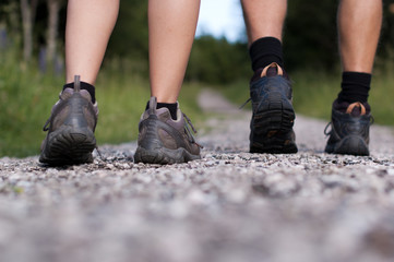Closeup of two pairs of hiking boots on a trail