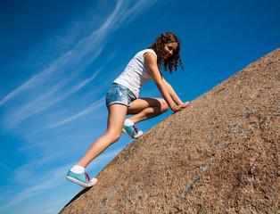 Young girl climbs the mountain