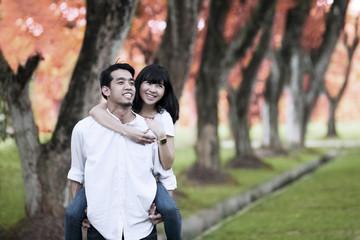 Asian couple piggy back