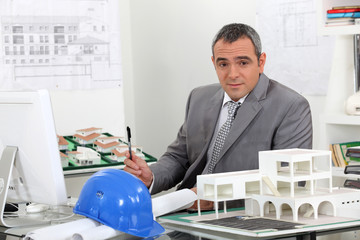 Architect in office surrounded by plans