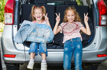 two little girls  sitting in the car with backpacks