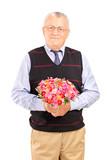 A mature gentleman holding bouquet of flowers