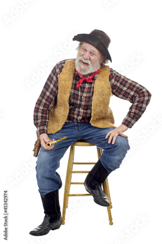 Cheerful old cowboy sits holding corn cob pipe