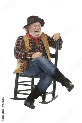 Laughing old cowboy sits in rocking chair