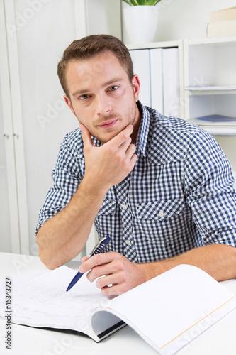 Junger Mann sitzend im Büro
