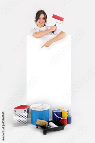 Female decorator stood pointing at blank poster