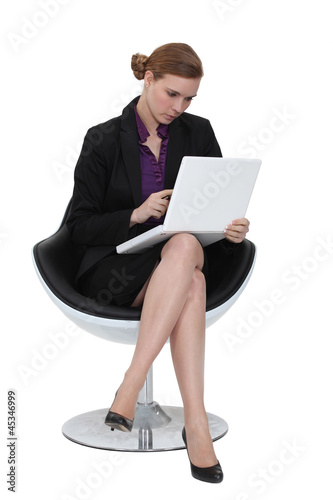 Businesswoman using a laptop in a chair