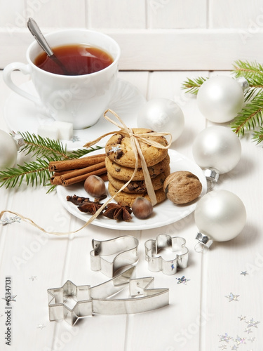 christmas biscuits and a cut of tea on white wooden background