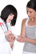 brunette nurse putting bandage on arm of female patient