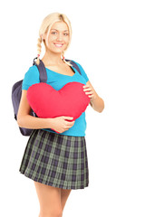 Blond beautiful student holding a heart shape object