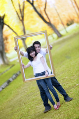Young couple with wooden frame