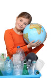 Young girl hugging a globe behind a box of plastic recycling