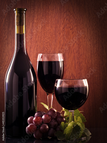 Red wine glass and Bottle on a wooden background