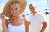 pretty blonde with sun hat and boyfriend in background
