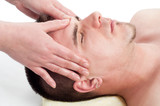 Young handsome man enjoying the facial massage on massage table