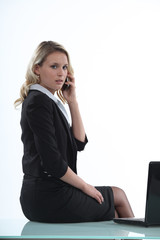 Woman sitting on her desk with a cellphone