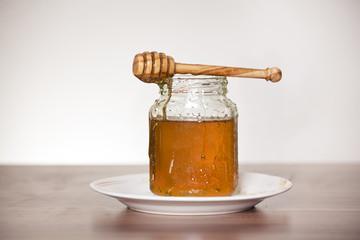 honigglas auf teller mit honiglöffel auf tisch