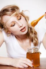 frau lässt honig vom löffel ins honigglas laufen