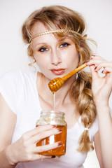 frau mit honigglas in hand lässt honig vom löffel laufen
