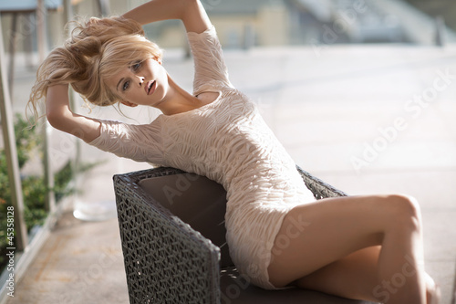 Blonde sitting on the armchair