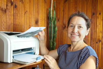 woman near the printer pulls paper