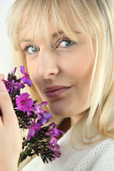 Blonde woman with a sprig of purple wild flowers