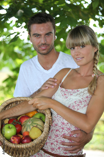 Young couple in park with fruit basket