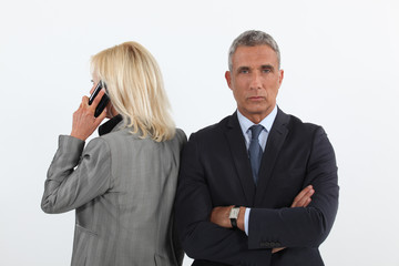 businessman waiting while his colleague is talking on her cell