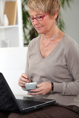Senior woman at home with laptop