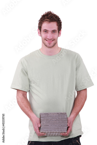 Man carrying pile of tiles