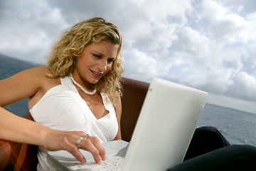 Woman sat at the coast with laptop