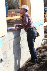 Foreman inspecting unfinished wooden house