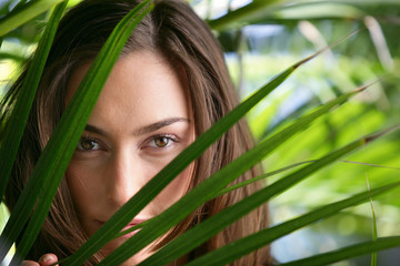 Sensual woman behind foliage