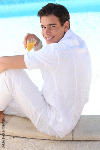 young man drinking cocktail on the beach
