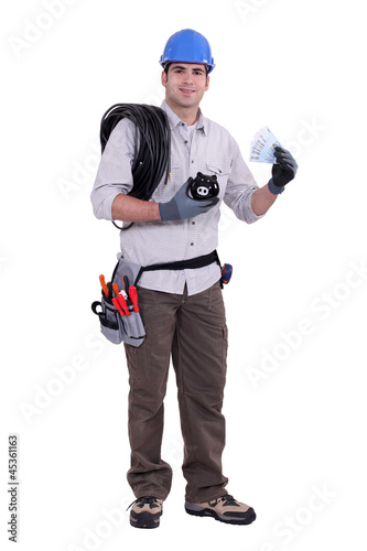 Construction worker holding a piggy bank and money