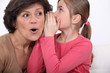 Girl whispering a secret to her grandmother