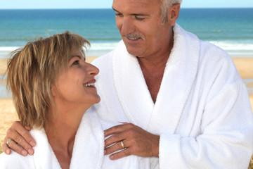 Couple wearing a bathrobe on a beach.