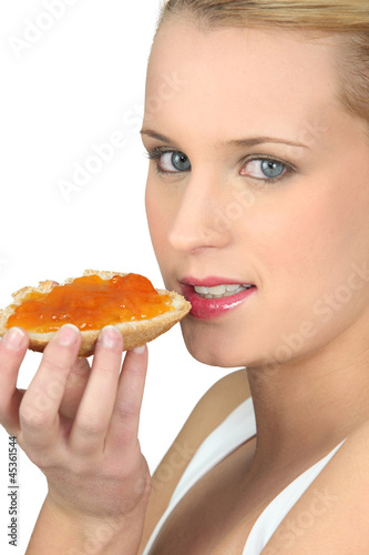 Woman eating a piece of bread with jam