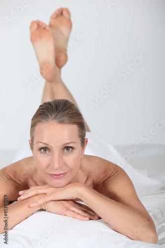 Woman lying naked under a white sheet