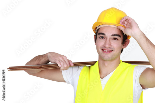 Construction worker carrying plywood